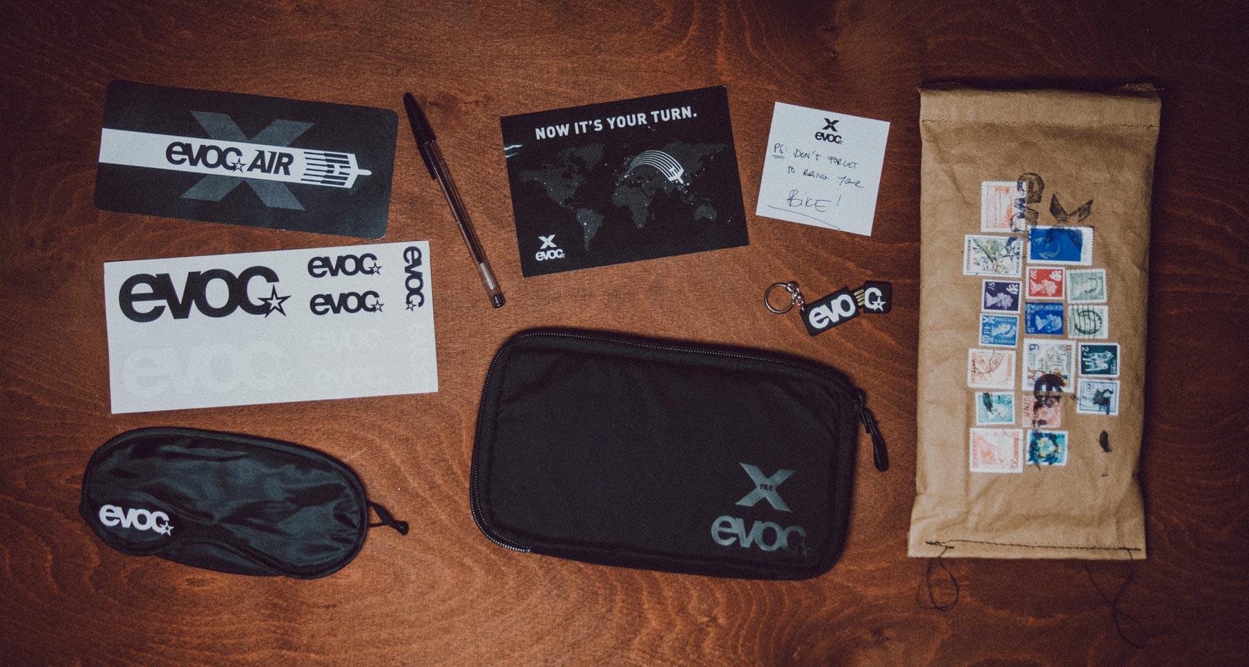 Man sieht alle Bestandteile des Einladungs-Mailing für Distributoren zum 10-Jährigen Jubiläum von evoc sports. Ein Flugticket, eine kleine Evoc-Tasche und ein Schlüsselanhänger sind u.a. abgebildet. Idee und Design sind von MAJORMAJOR.