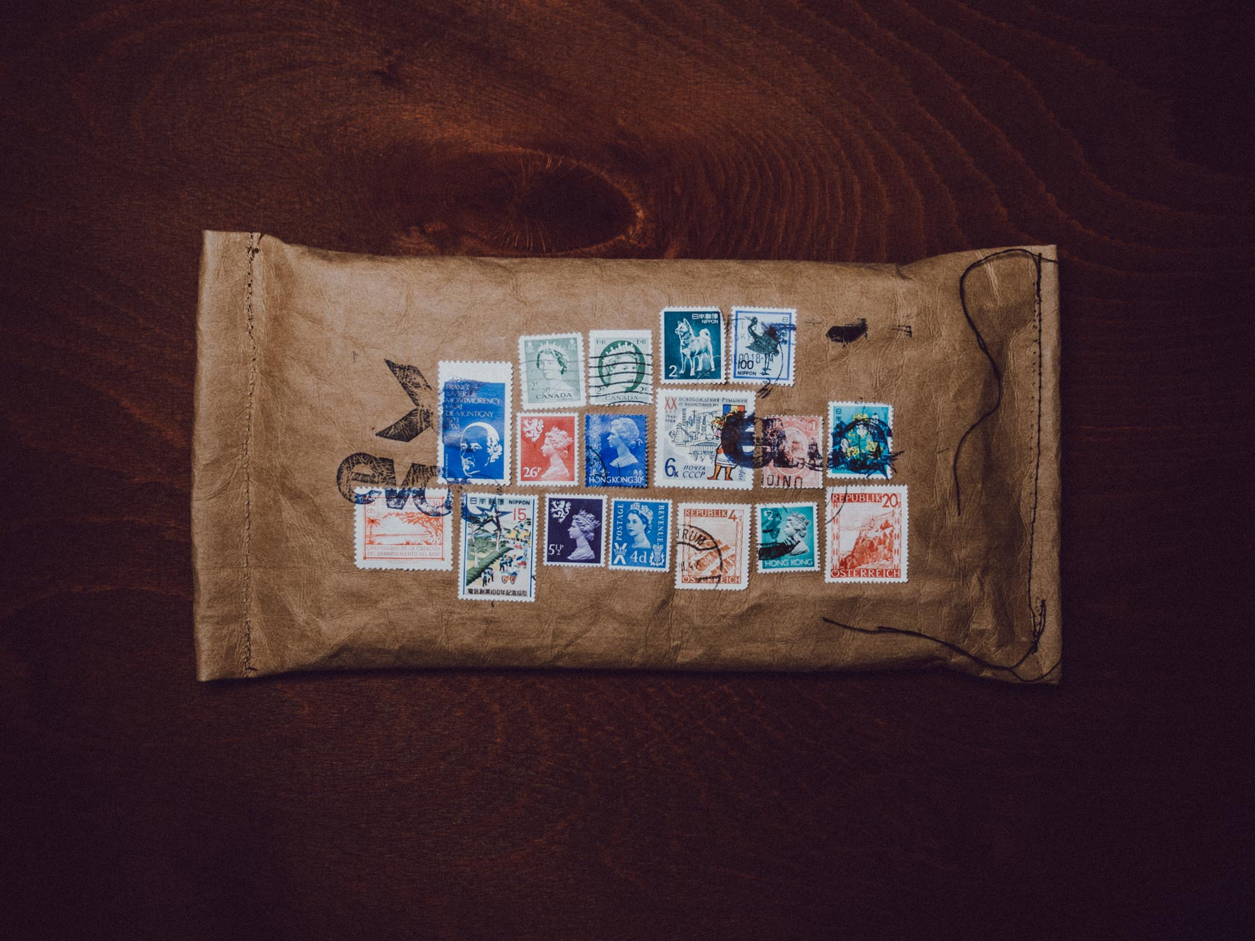 Man sieht das Einladungs-Mailing für Distributoren zum 10-Jährigen Jubiläum von evoc sports. Ein Kuvert aus Jeans-Label-Material mit bunten Briefmarken aus 10 Ländern ist abgebildet. Idee und Design sind von MAJORMAJOR.