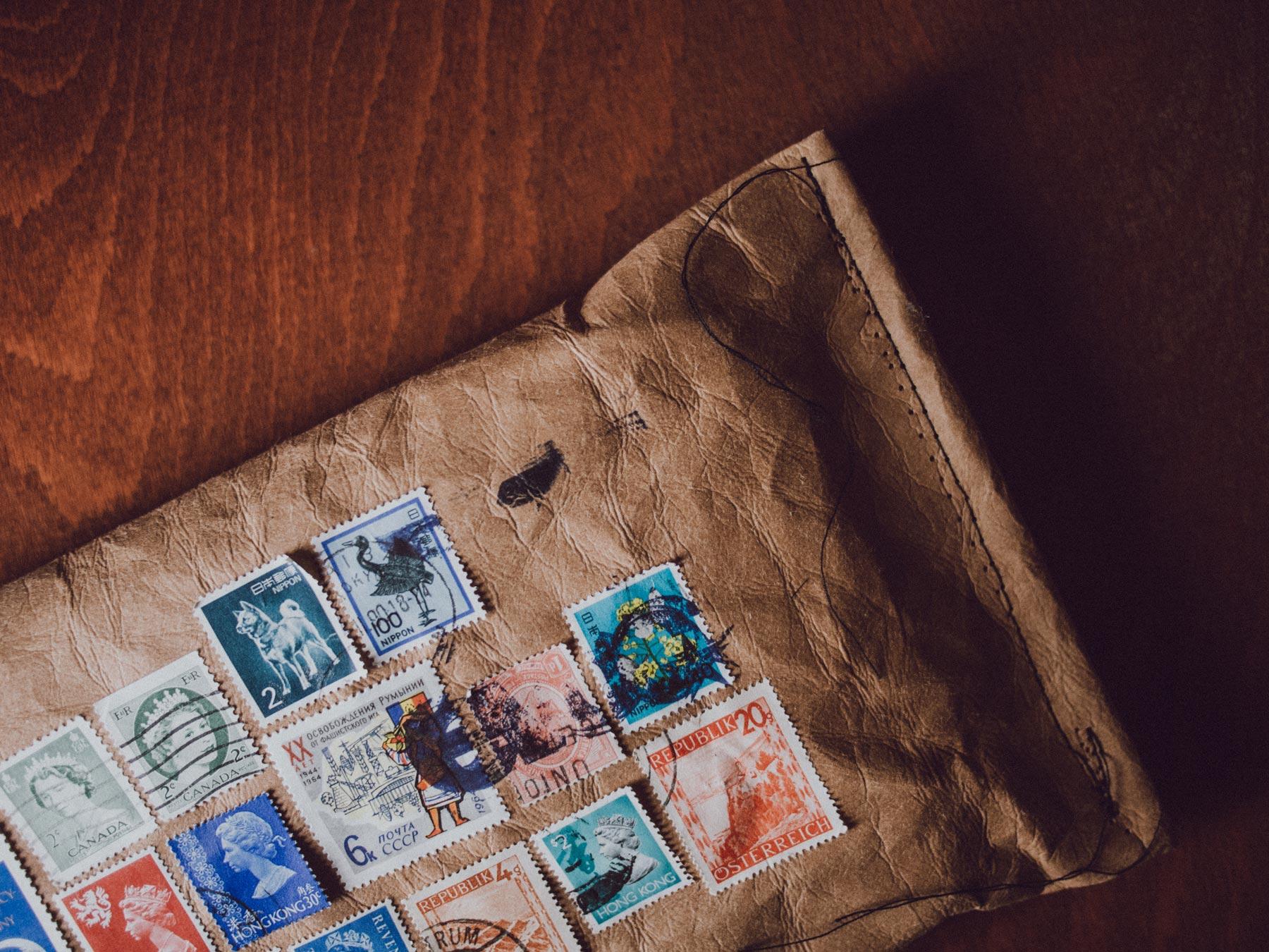 Man sieht den rechten Teil des Einladungs-Mailing für Distributoren zum 10-Jährigen Jubiläum von evoc sports. Ein Kuvert aus Jeans-Label-Material mit bunten Briefmarken aus 10 Ländern ist abgebildet. Idee und Design sind von MAJORMAJOR.