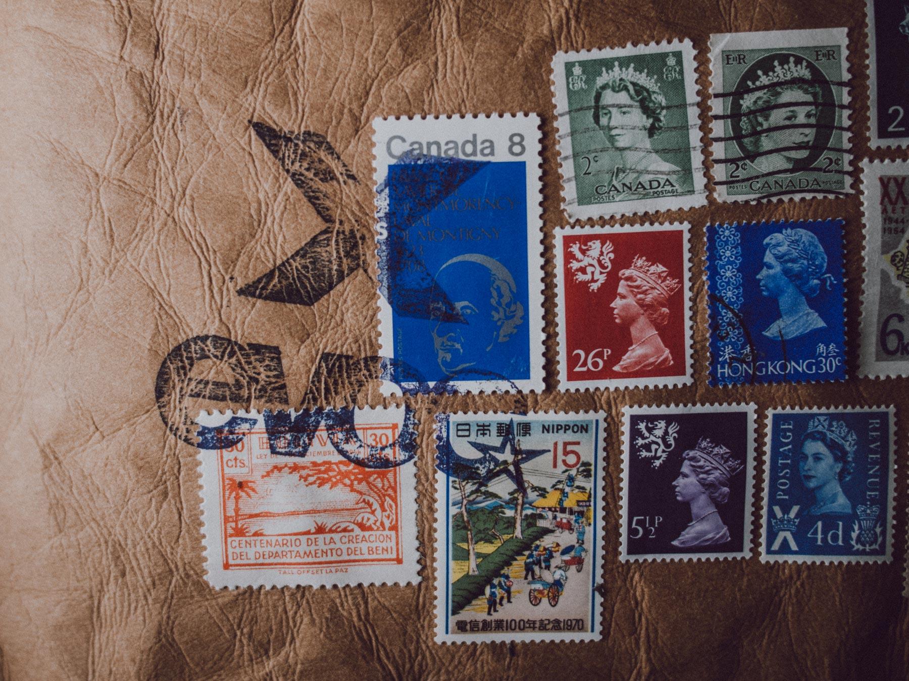 Man sieht den oberen rechten Teil des Einladungs-Mailing für Distributoren zum 10-Jährigen Jubiläum von evoc sports. Ein Kuvert aus Jeans-Label-Material mit bunten Briefmarken aus 10 Ländern ist abgebildet. Idee und Design sind von MAJORMAJOR.