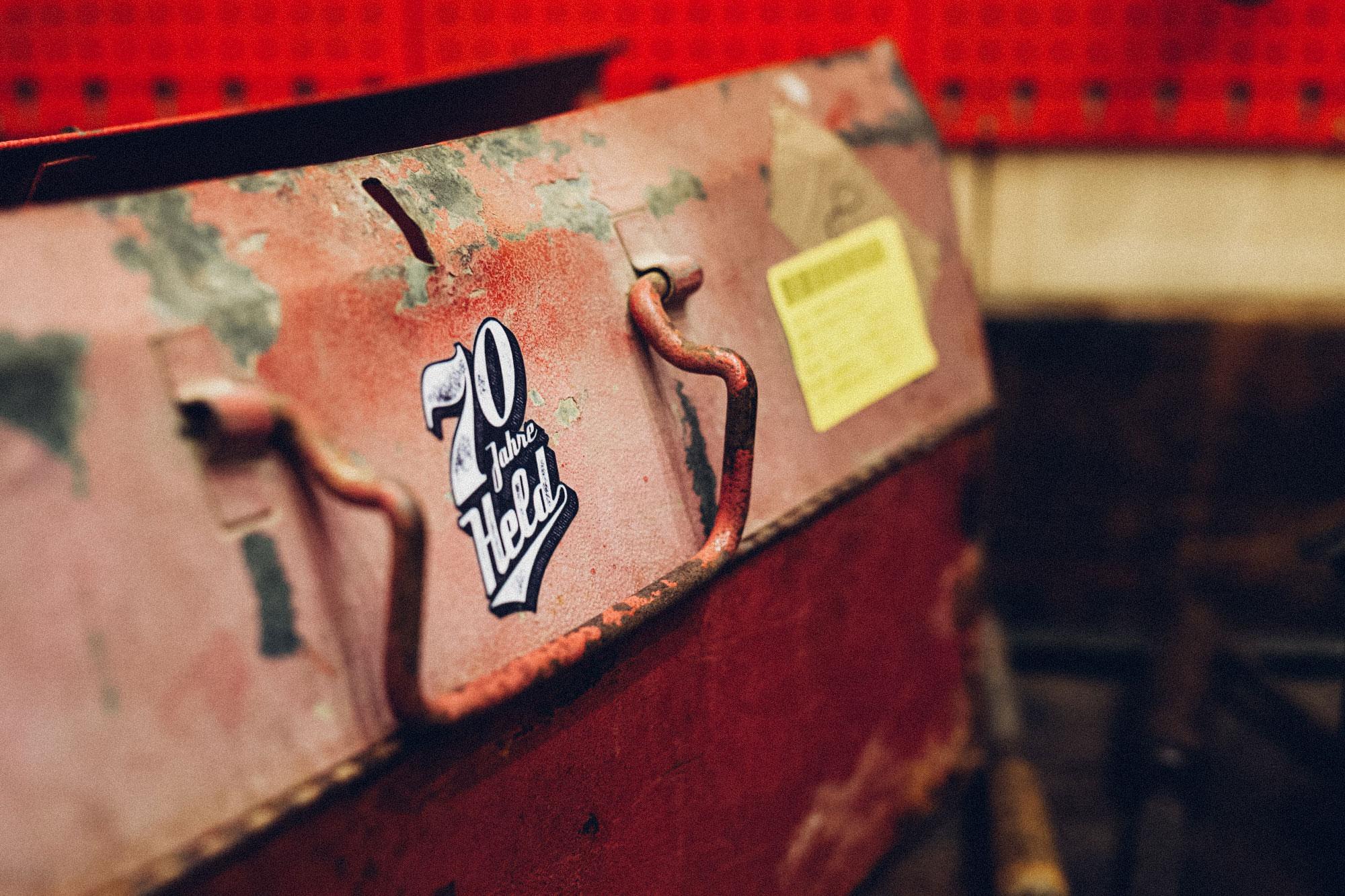 Ein Foto des 70-Jahre-Held-Messestandes. Man sieht das 70-Jahre-HELD-Logo von Held Bikerfashion aufgebracht auf einer alten Mulde. Das Design stammt von MAJORMAJOR.