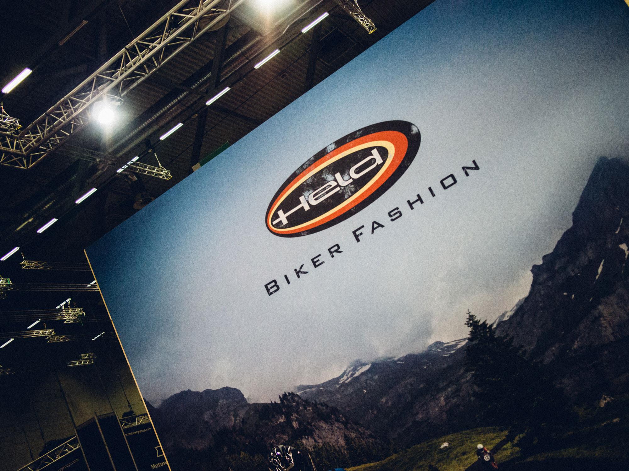 Ein Banner des 70-Jahre-Held-Messestandes. Man sieht ein Motorrad, das eine schöne Bergstraße entlang fährt. Das Logo von Held Bikerfashion ist oben im Bild zu sehen. Das Design stammt von MAJORMAJOR.
