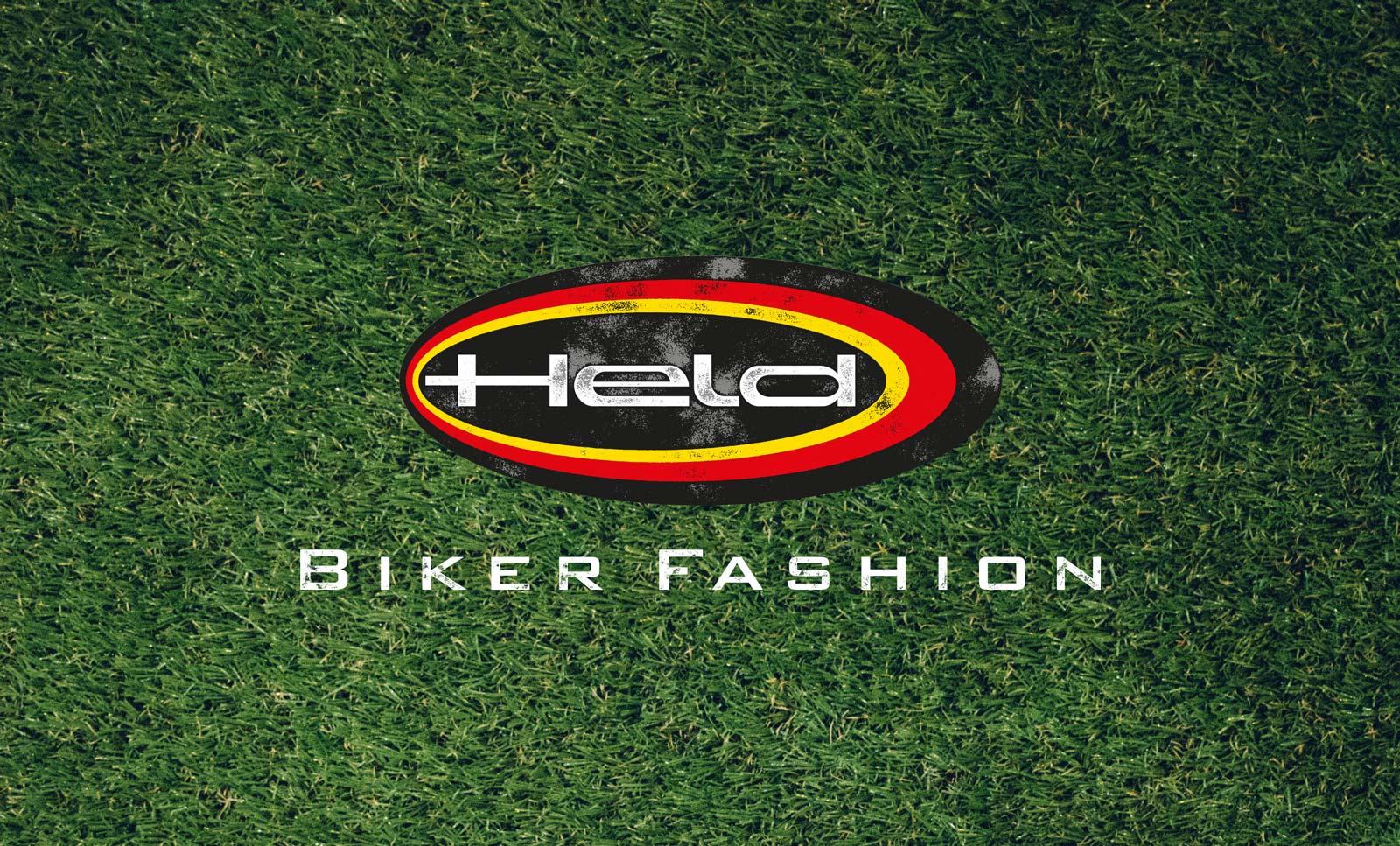 Ein Banner des 70-Jahre-Held-Messestandes. Man sieht das Logo von Held Bikerfashion auf grünem Rasen liegen. Das Design stammt von MAJORMAJOR.