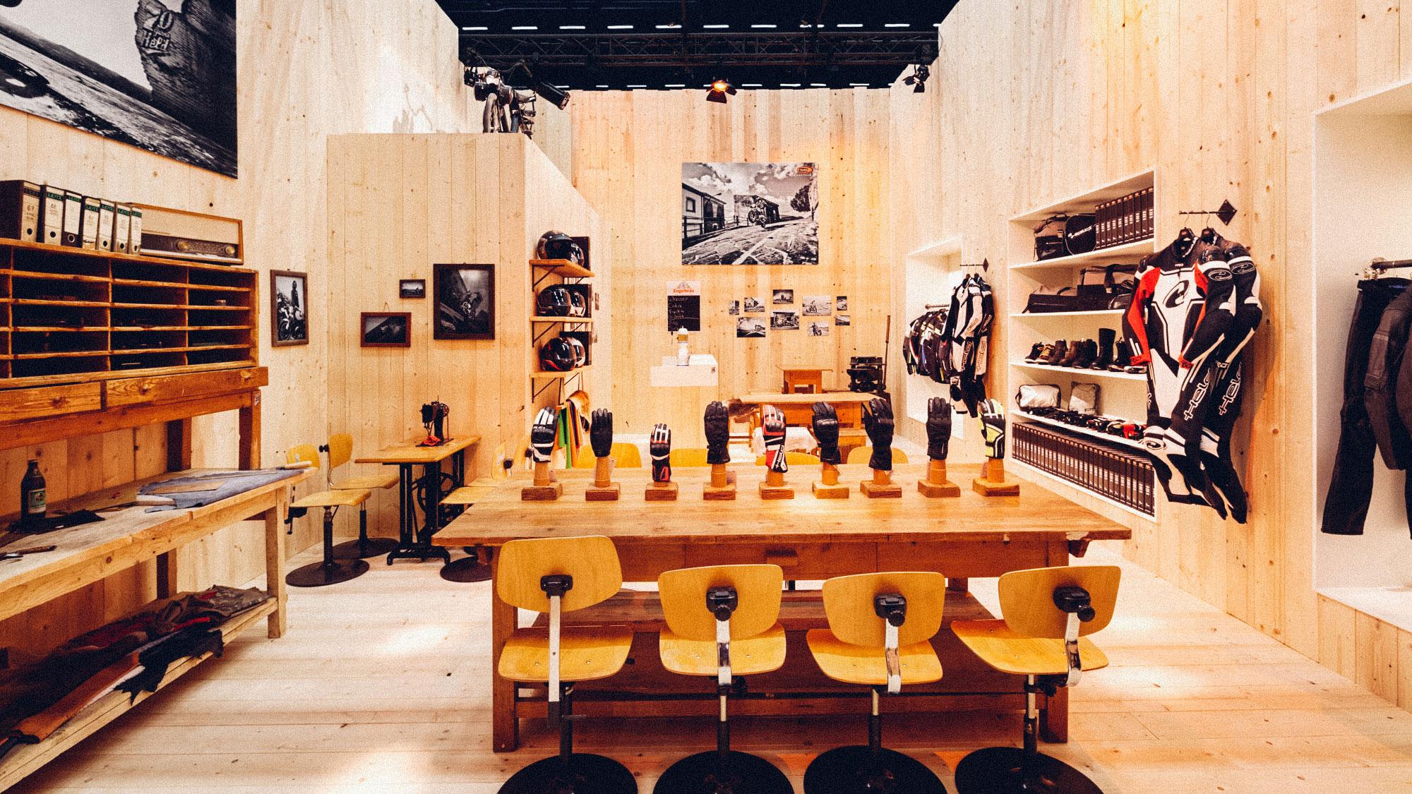 Ein Foto des Besprechungsraumes des 70-Jahre-Held-Messestandes. Alles ist im Stil einer Berghütte gehalten, im Vordergrund ein Schreibtisch mit den aktuellen HELD-Motorrad-Handschuhen. Konzept und Design sind von MAJORMAJOR.