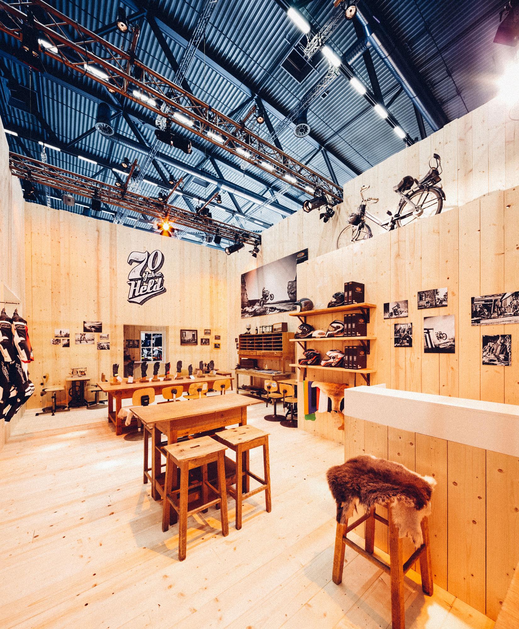 Ein Foto des Besprechungsraumes des 70-Jahre-Held-Messestandes. Alles ist im Stil einer Berghütte gehalten, im Vordergrund die Bar, im Hintergrund ein Schreibtisch mit den aktuellen HELD-Motorrad-Handschuhen. Konzept und Design sind von MAJORMAJOR.