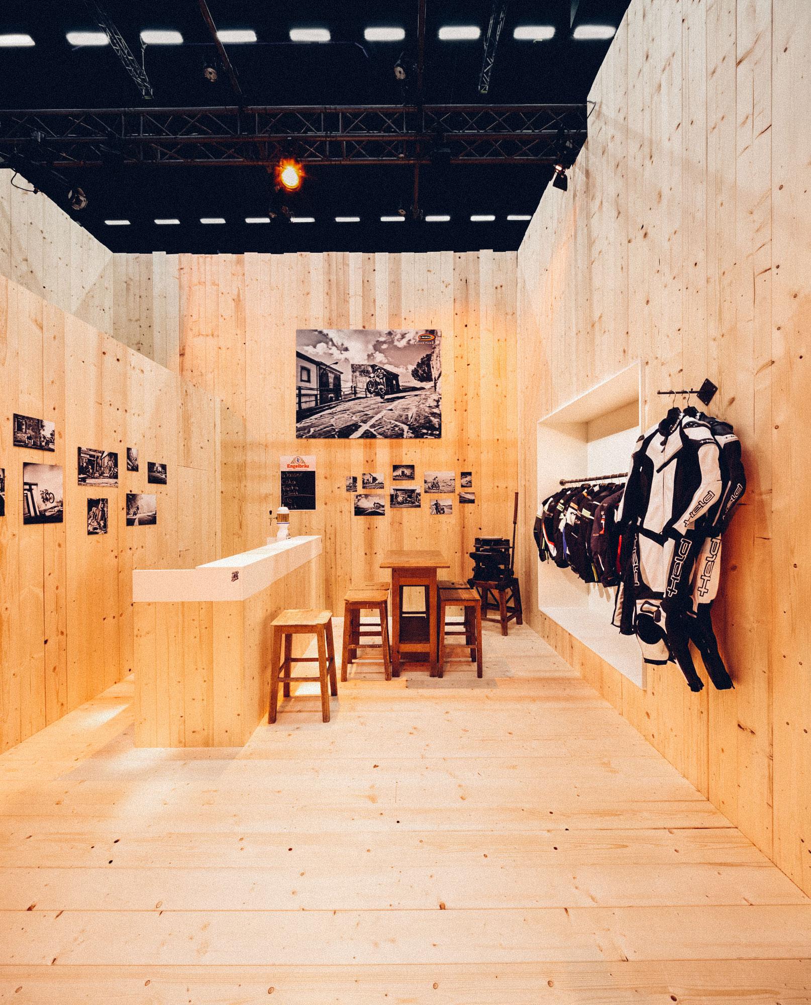 Ein Foto des Besprechungsraumes des 70-Jahre-Held-Messestandes. Alles ist im Stil einer Berghütte gehalten, links sieht man die Bar und rechts Garderoben mit aktueller HELD-Lederkombi. Konzept und Design sind von MAJORMAJOR.