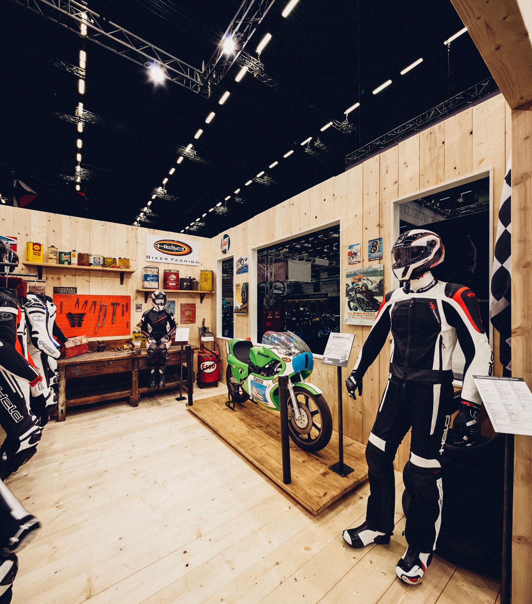 Ein Foto aus dem inneren des Paddocks des 70-Jahre-Held-Messestandes. Man sieht eine alte Renn-Kawasaki und die aktuellen Lederkombis von Held Bikerfashion. Konzept und Design sind von MAJORMAJOR.