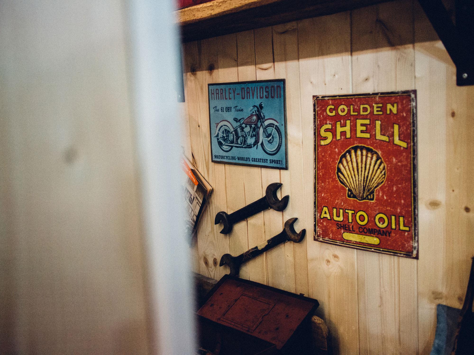 Ein Foto aus dem Inneren des Paddocks des 70-Jahre-Held-Messestandes. Man sieht eine Werkstatt-Wand mit alten Emaille-Schildern von Shell und Harley Davidson. Konzept und Design sind von MAJORMAJOR.