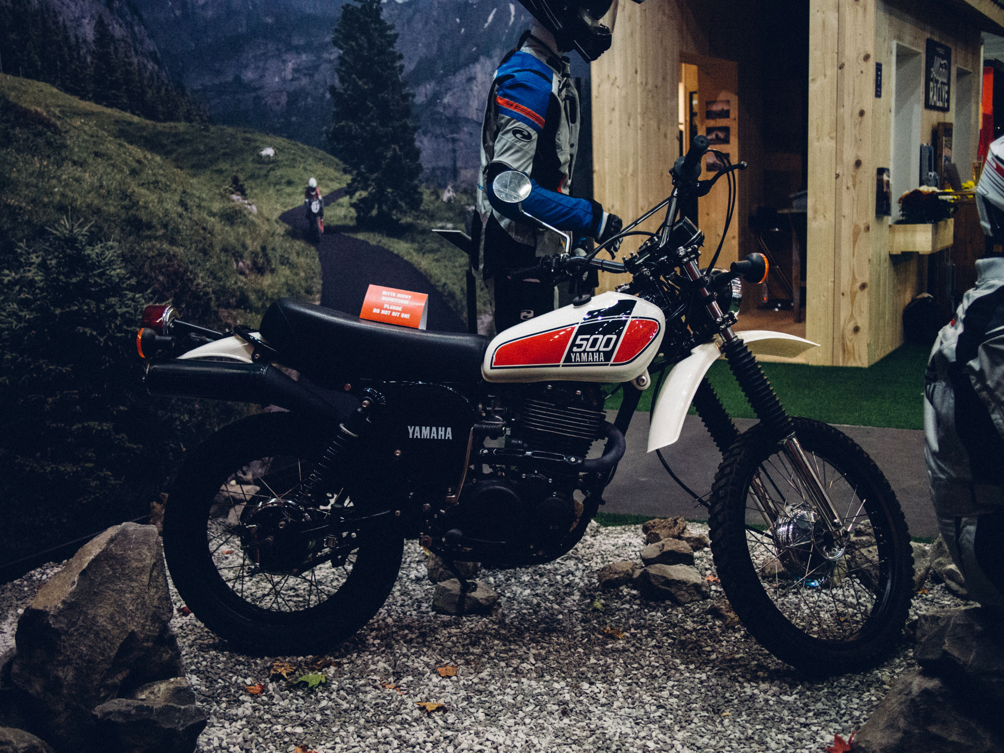 Ein Foto des 70-Jahre-Held-Messestandes. Im Vordergrund die Kult-Enduro Yamaha XT 500 vor einer Bergrennen-Szenerie mit Berghütte und auf echten Schotterpiste stehend. Konzept und Design sind von MAJORMAJOR.