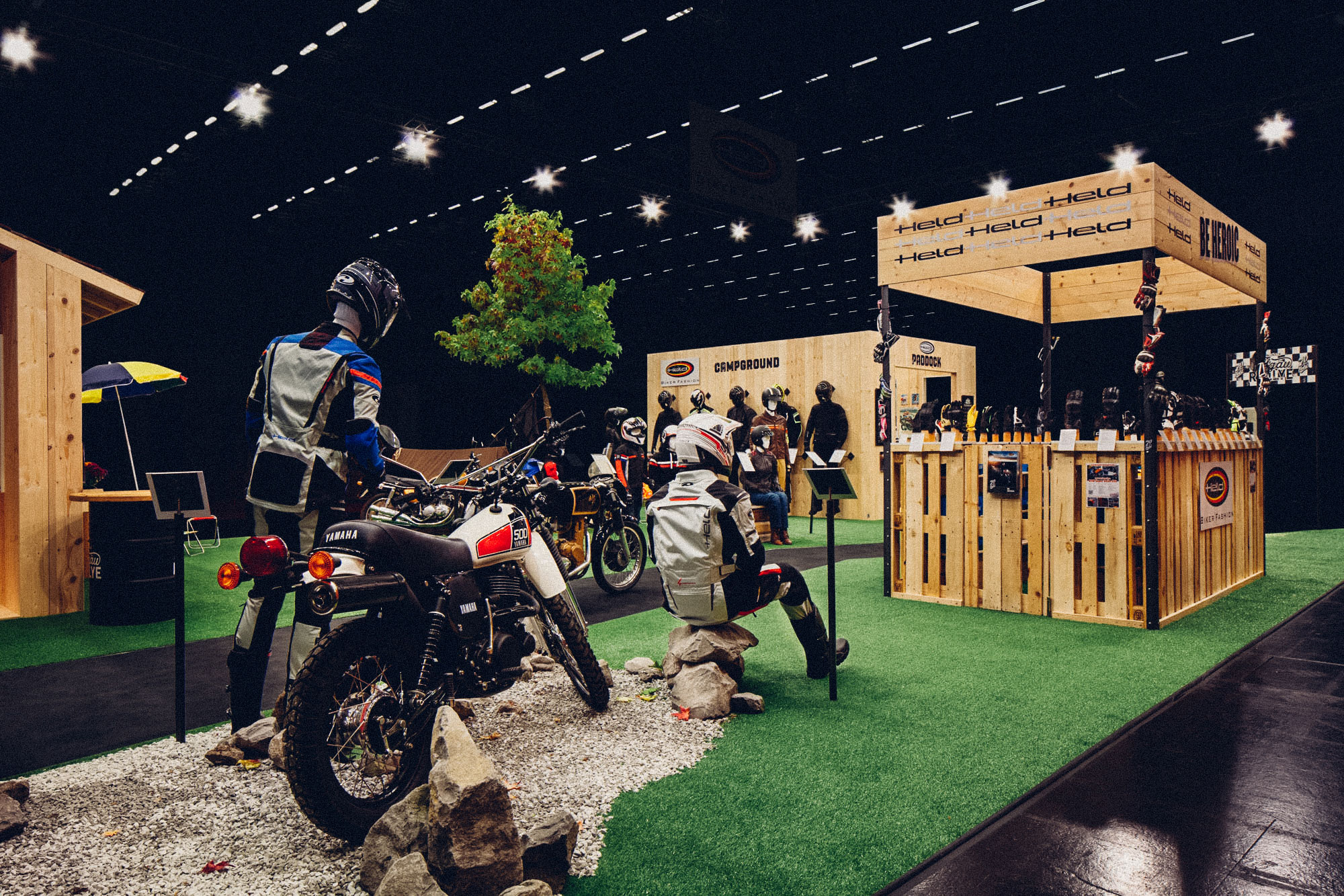 Ein Foto des 70-Jahre-Held-Messestandes aus Dreiviertel-Perspektive. Im Vordergrund die Kult-Enduro Yamaha XT 500 auf echter Schotterpiste stehend. Dahinter Paddock und Merch-Stand. Konzept und Design sind von MAJORMAJOR.