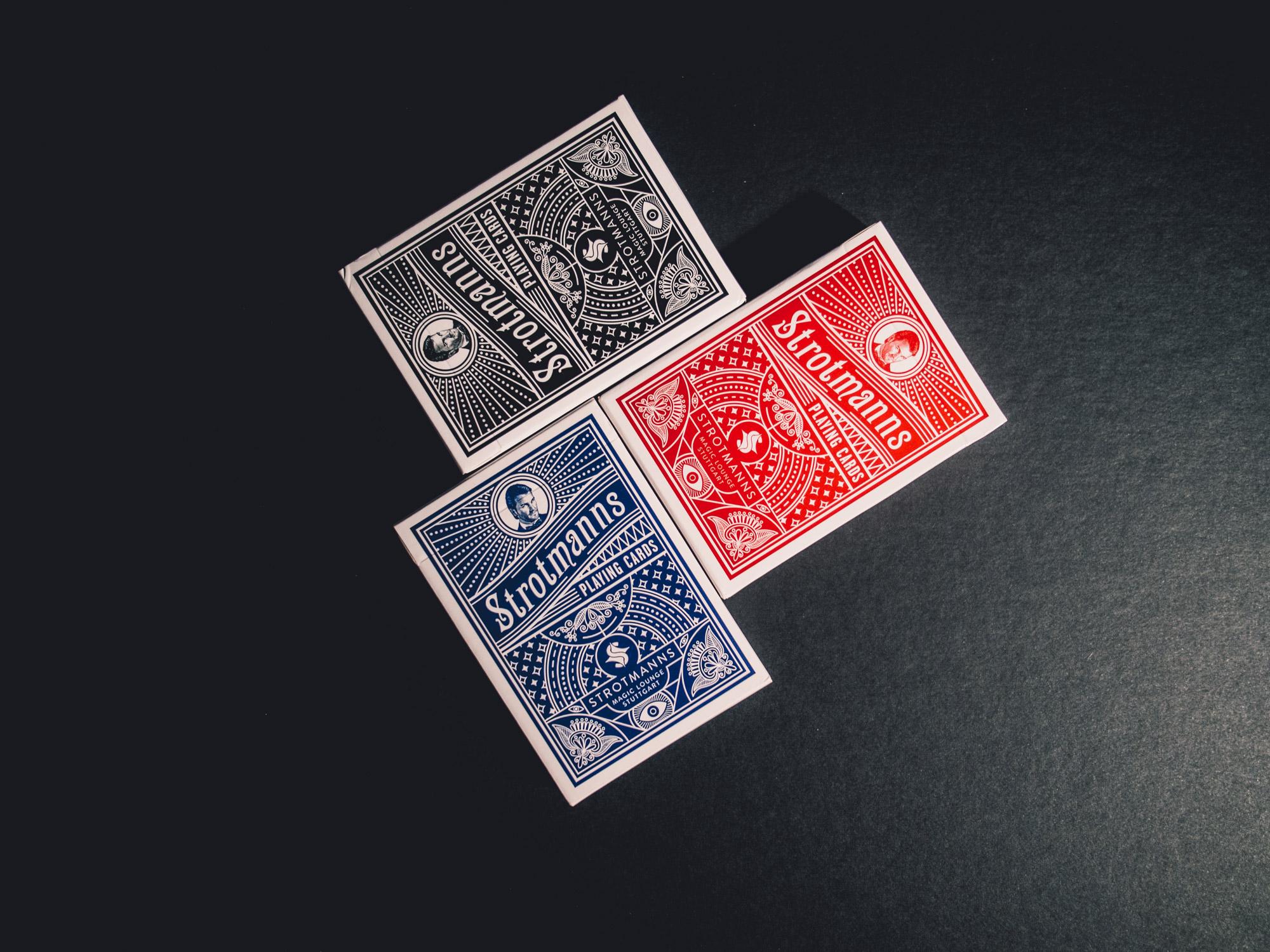 Man sieht 3 Spielkarten-Sets der Strotmanns Magic Lounge in den drei verfügbaren Farben schwarz, rot und blau. Die Gestaltung ist an klassische amerikanische Poker-Playingcards angelehnt. Das Design ist von MAJORMAJOR.