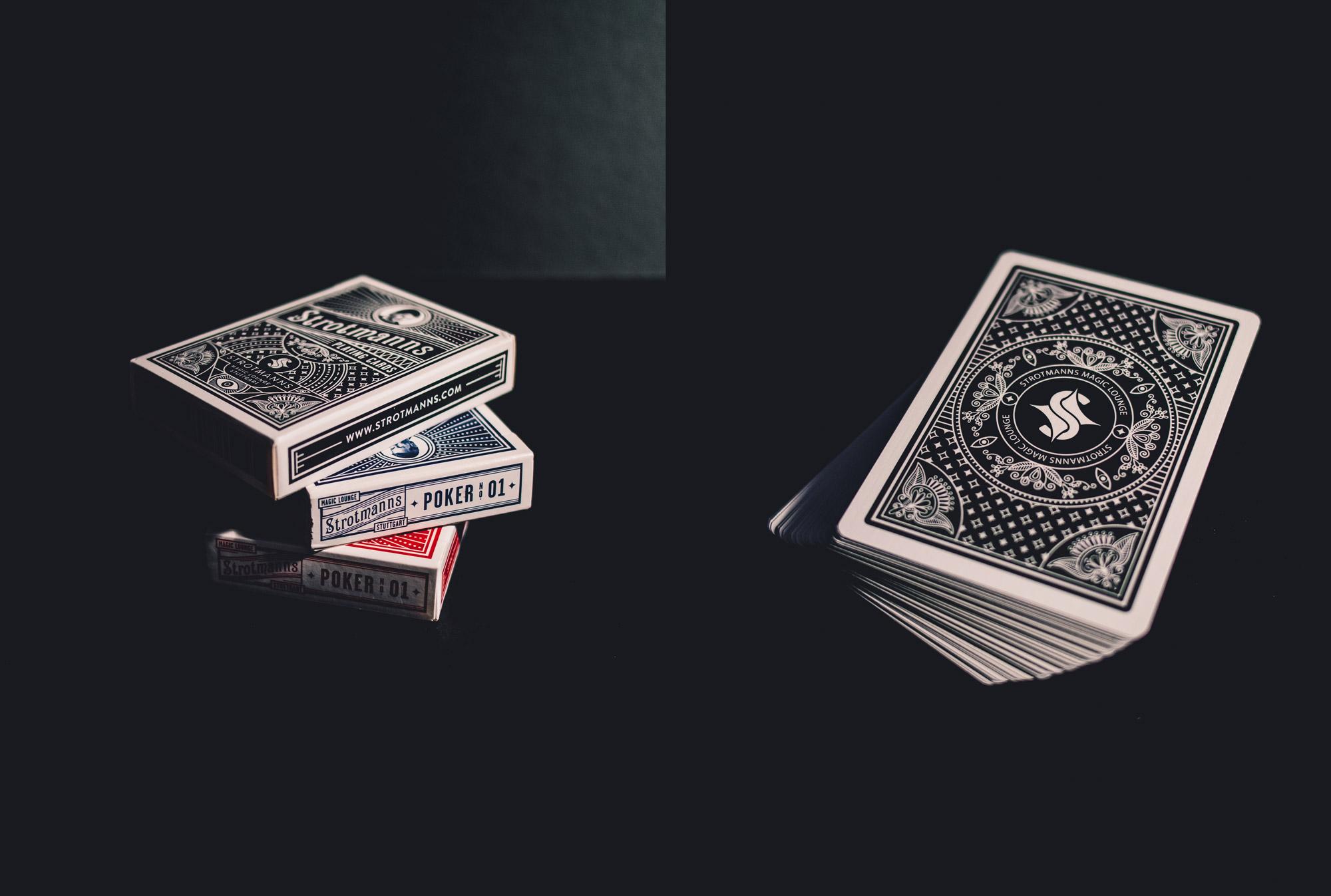 Man sieht links 3 gestapelte Spielkarten-Sets der Strotmanns Magic Lounge, rechts davon einen Stapel mit Spielkarten. Die Gestaltung ist an klassische amerikanische Poker-Playingcards angelehnt. Das Design ist von MAJORMAJOR.