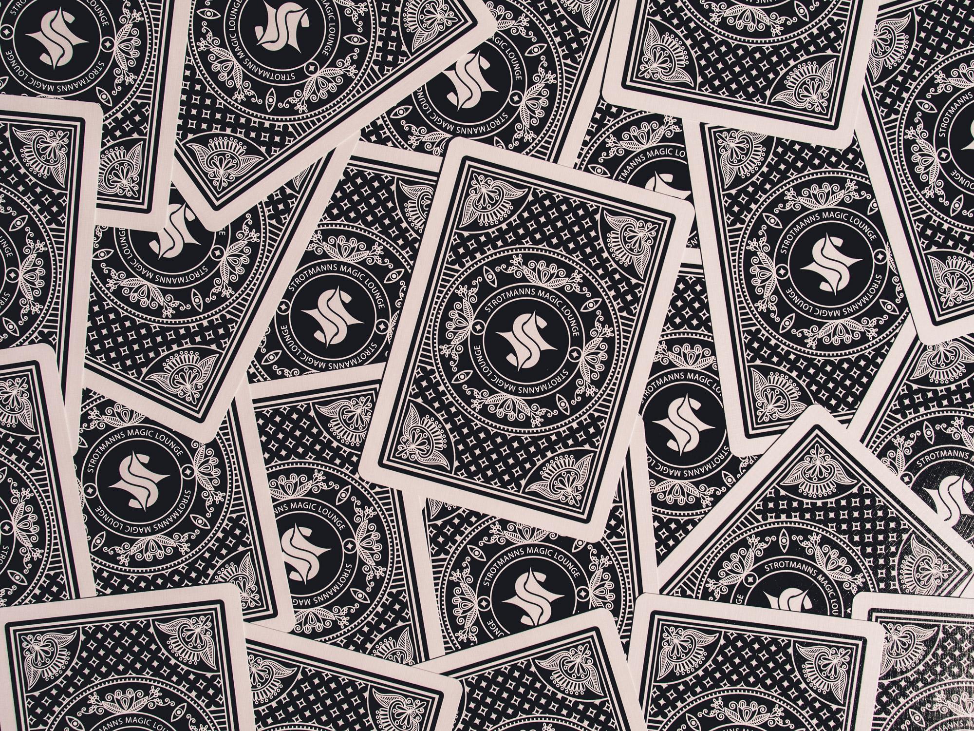 Man sieht viele Rückseiten von Spielkarten der Strotmanns Magic Lounge. Die Karten überlappen sich. Das Rückseiten-Muster ist gestalterisch an klassische amerikanische Poker-Playingcards angelehnt. Das Design ist von MAJORMAJOR.