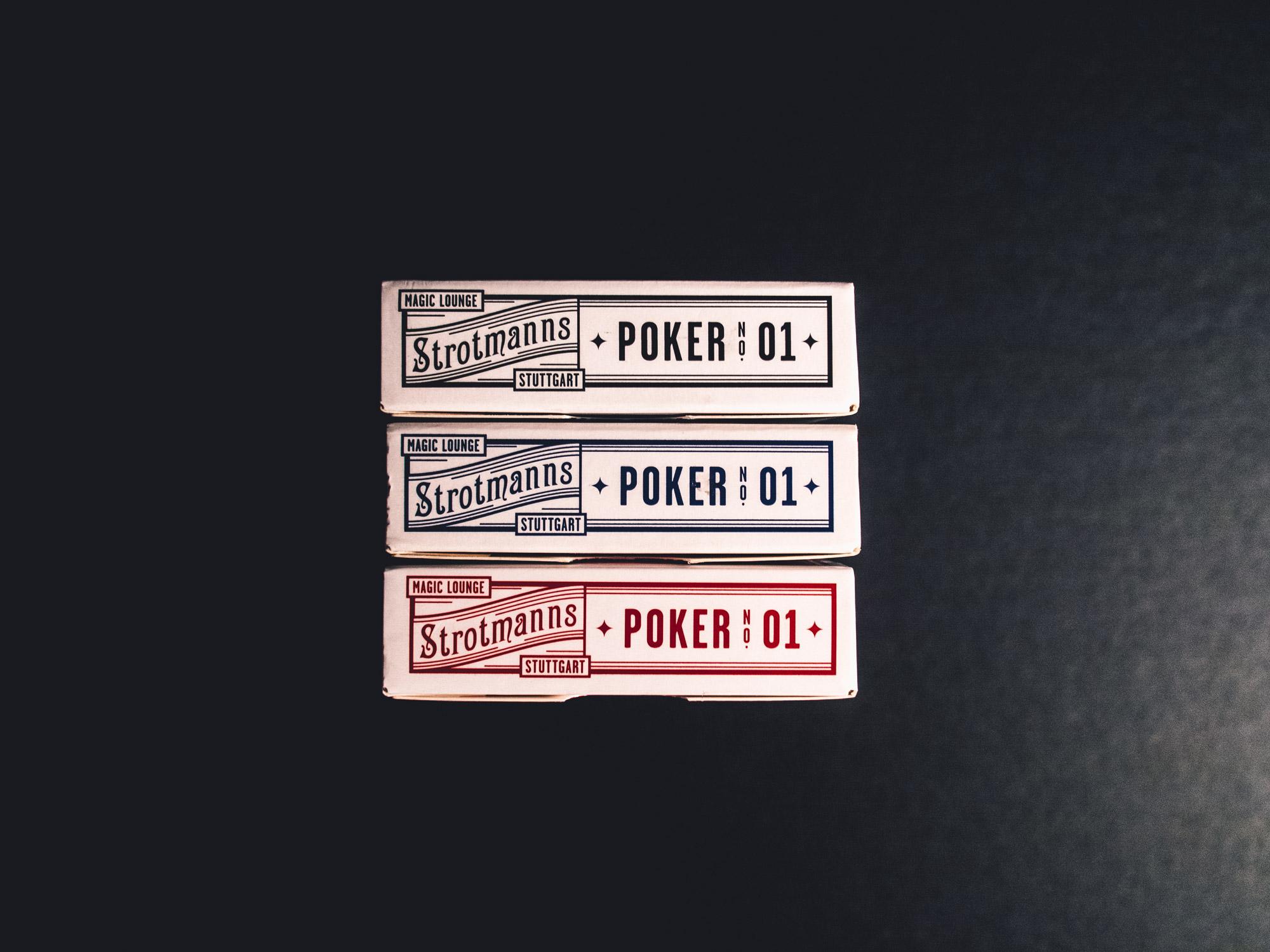 Man sieht die Kopfseite von Spielkarten-Sets der Strotmanns Magic Lounge in den drei verfügbaren Farben schwarz, rot und blau. Die Gestaltung ist an klassische amerikanische Poker-Playingcards angelehnt. Das Design ist von MAJORMAJOR.
