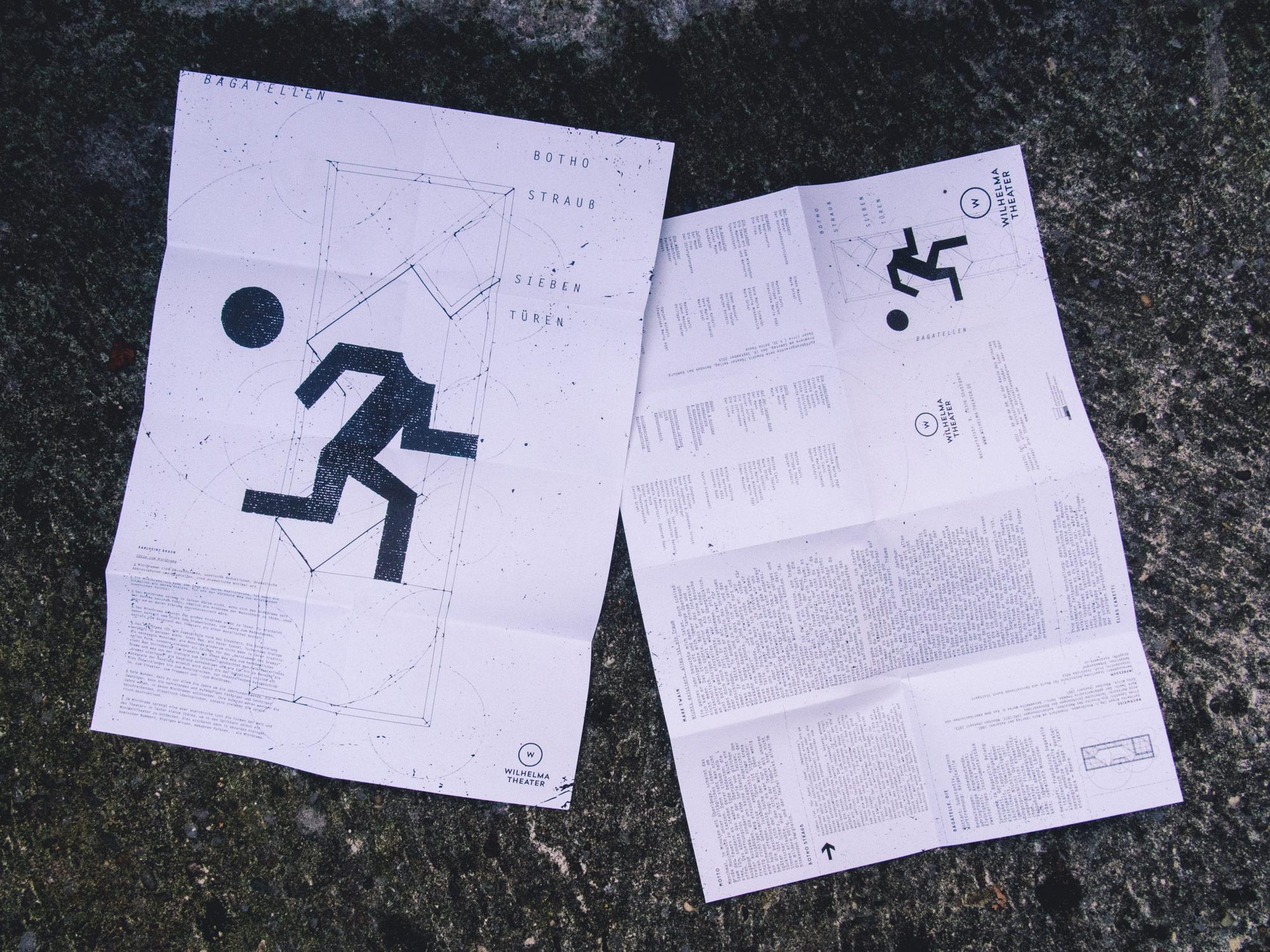 Man sieht zwei Programmhefte auf einer Mauer liegen. Links den Titel zum Stück