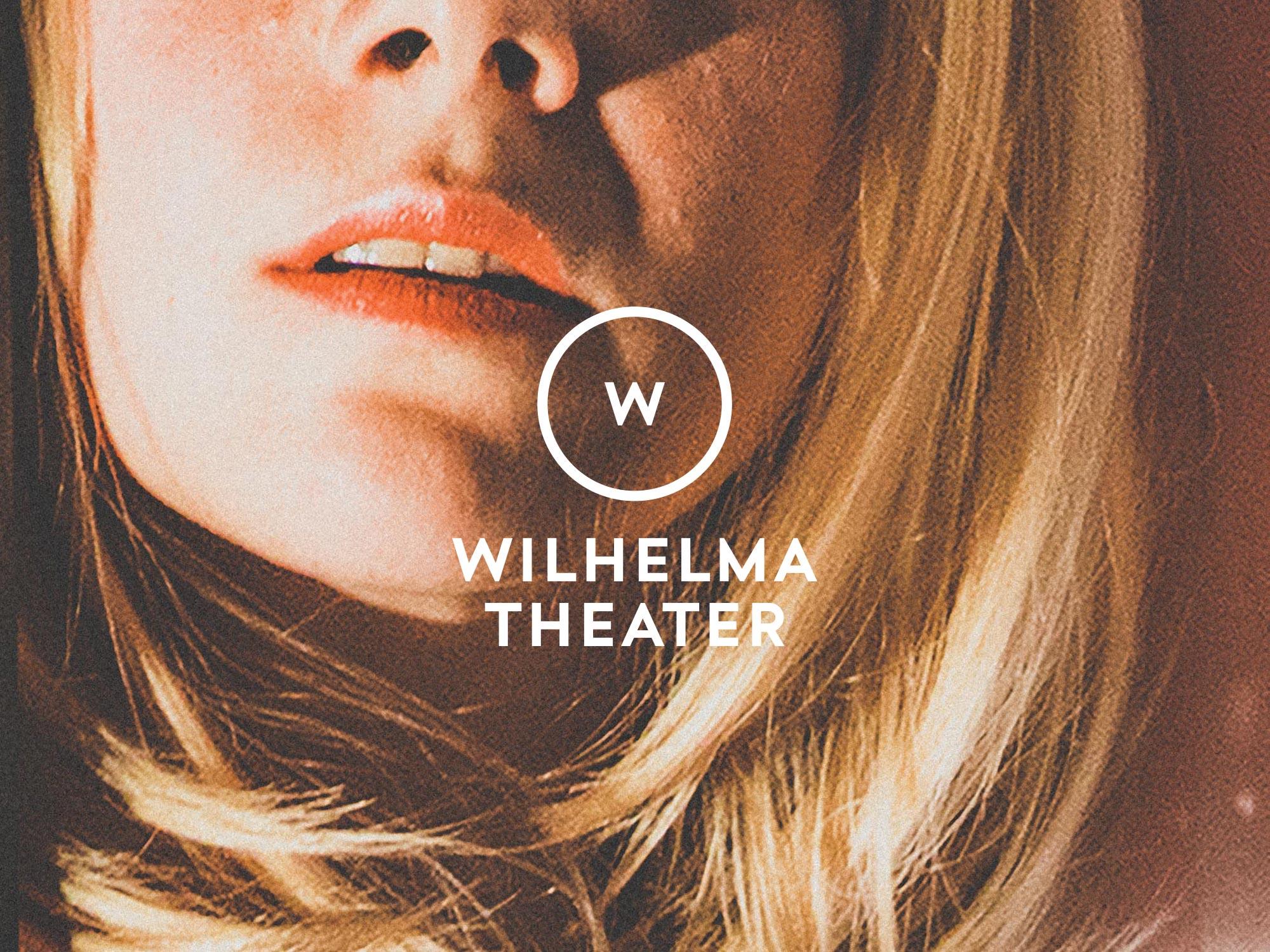 Man sieht ein Plakat für das Wilhelma Theater Stuttgart. Zu sehen ist die untere Hälfte eines Frauengesichtes, der Fokus liegt auf Mund und sinnlichen Lippen. Das neue Logo des Wilhelma Theaters liegt mittig über dem Gesicht. Das Design ist von MAJORMAJOR.