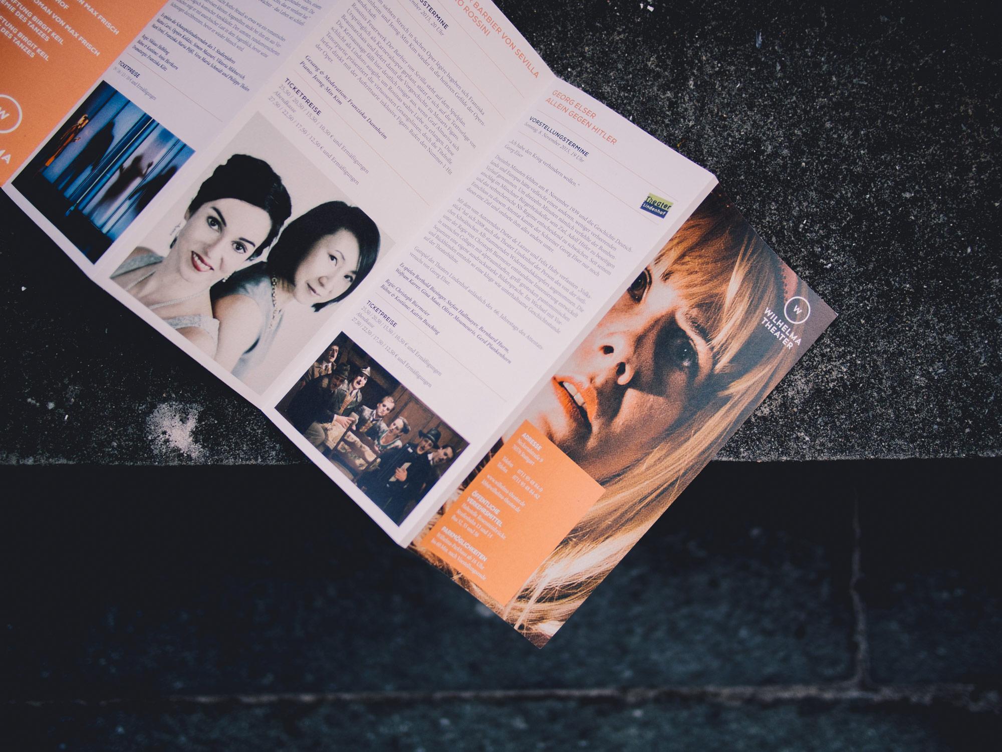 Man sieht den Umschlag und Innenseiten des Programmhefts des Wilhelma Theaters Stuttgart. Das Heft liegt auf einer Mauer, auf dem aufgeschlagenen Titel ist das Gesicht einer blonden Frau zu sehen. Das Design ist von MAJORMAJOR.