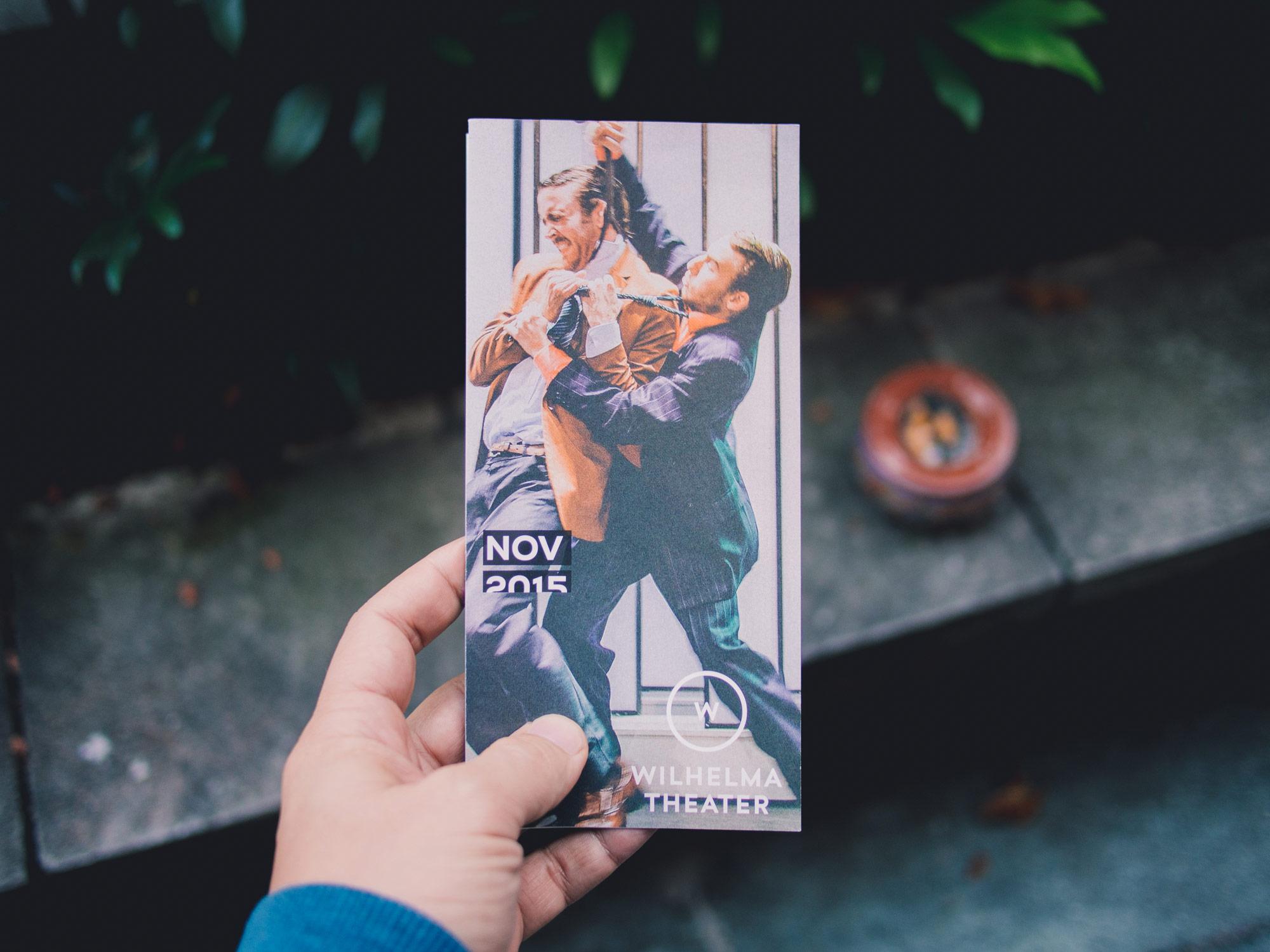 Man sieht den Titel des Programmhefts des Wilhelma Theaters Stuttgart. Das Heft wird von einer Hand gehalten, auf dem Titel sieht man 2 Männer in Anzügen kämpfen. Das Design ist von MAJORMAJOR.