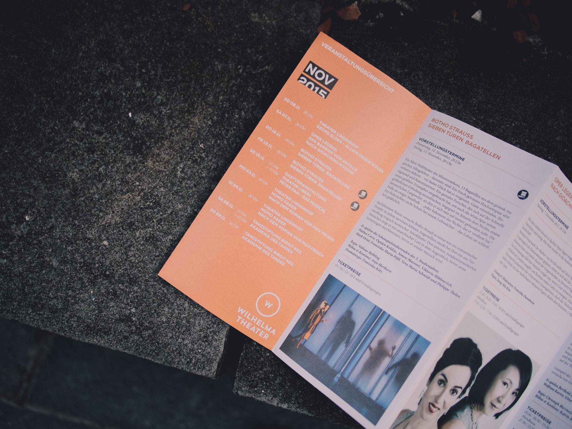 Man sieht die Innenseiten des Programmhefts des Wilhelma Theaters Stuttgart. Das Heft liegt auf einer Mauer, auf den Seiten sieht man 2 Bilder mit Schauspielern aktueller Stücke. Das Design ist von MAJORMAJOR.